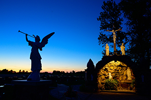 A grotto depicting Our Lady of Lourdes and a Crucifixion scene is pictured after sunset July 23, 2020, in the cemetery of St. Francis and St. Mary Church in Brussels, Wis. (CNS photo/Sam Lucero, The Compass)